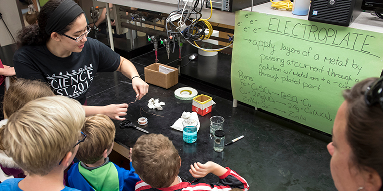 IU student is performing a scientific experiment in front of an audience of children.