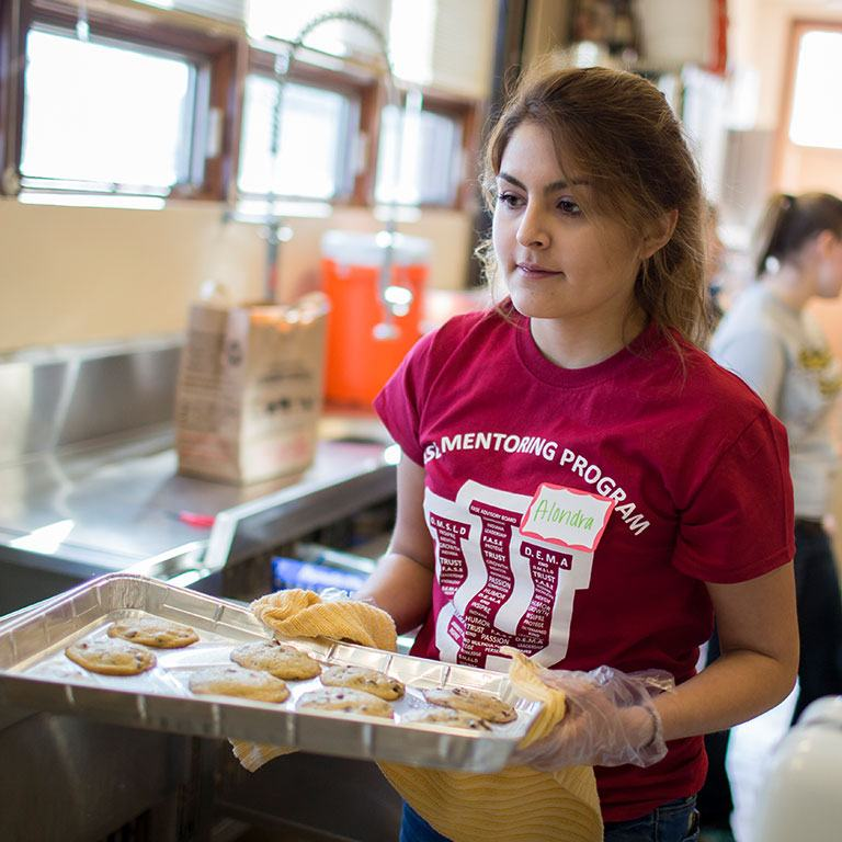 IU student volunteering at MLK Day of Service. She is holding a tray of fresh baked cookies.