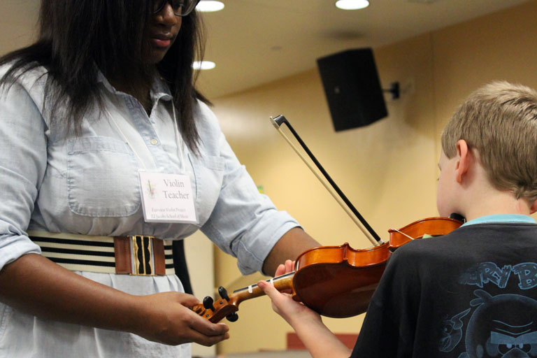 IU student teaching a child how to play the violin.